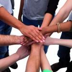 Hände, die im Kreis stehender junger Menschen in die Mitte aufeinander gelegt werden.