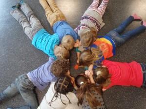 Kinder liegen im Kreis auf dem Boden